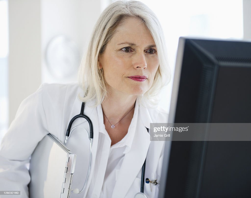 Confident female doctor using computer : Stock Photo