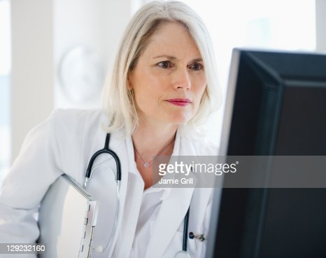 Confident female doctor using computer : ストックフォト