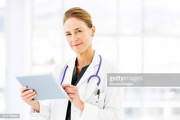 Confident Female Doctor Using Tablet Computer