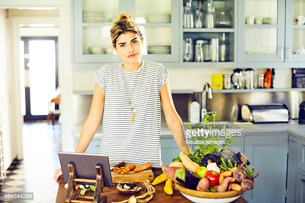 Confident female with vegetables and digital tablet in kitchen
