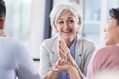 Cheerful female financial advisor gives advice to young couple during meeting.