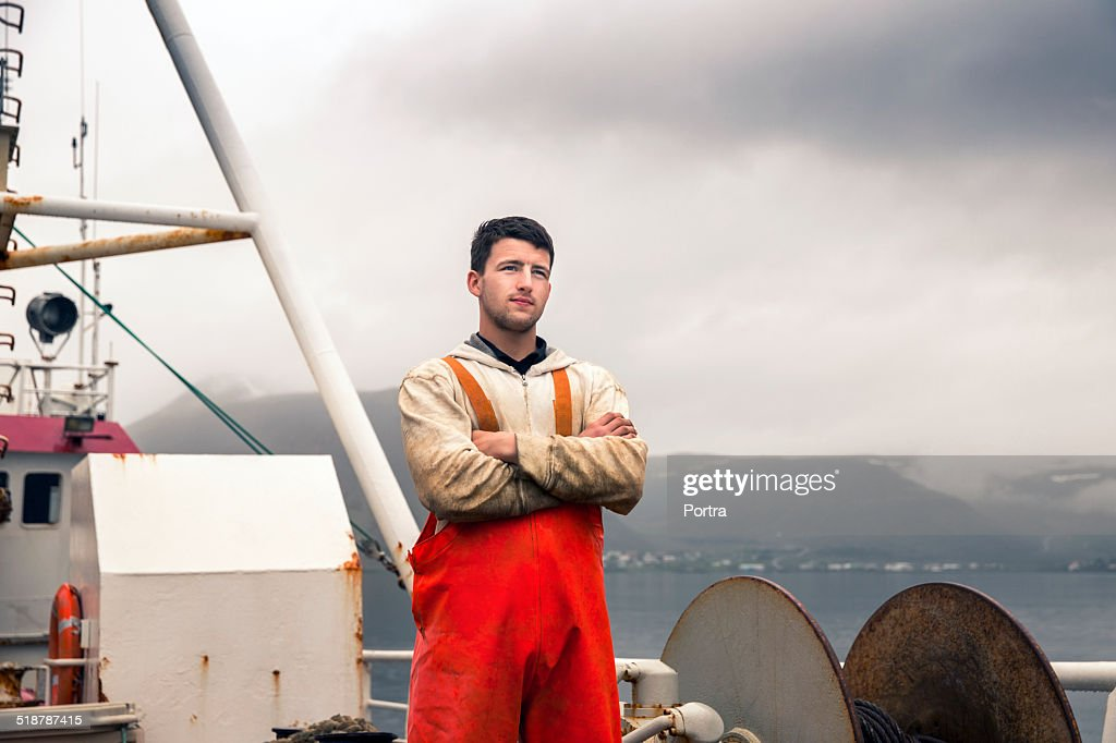 Confident fisherman standing on fishing boat