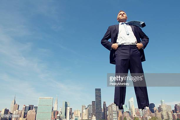 Confident Giant Businessman Standing Tall Over City Skyline
