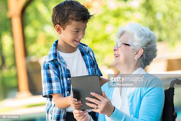 Confident grandson teaches his grandmother how to use tablet