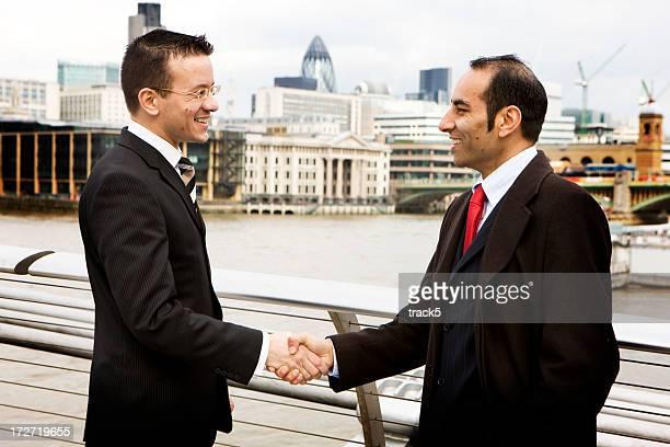 Confident handshake between a diverse pair of London businessmen