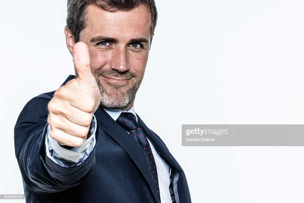 confident handsome young businessman smiling, showing thumbs up in foreground : Stock Photo