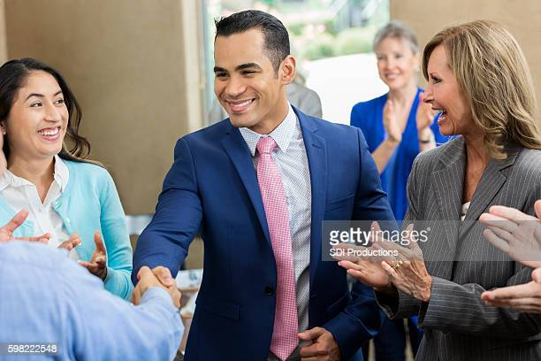 Confident Hispanic businessman shakes hands with colleague