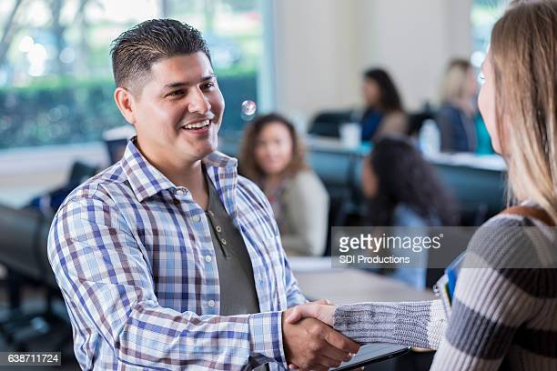 Confident Hispanic college professor greets student