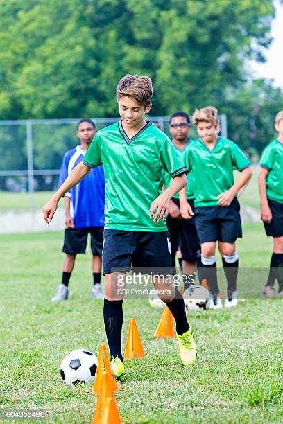 Confident Hispanic teenage soccer player at soccer practice