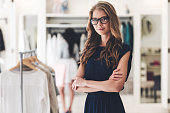 Beautiful young woman in glasses keeping arms crossed and looking at camera while standing at the clothing store