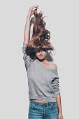 Attractive young woman stretching her hair up and while standing against grey background