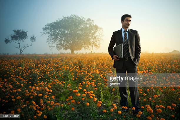Confident Indian businessman with laptop standing in marigold farm field