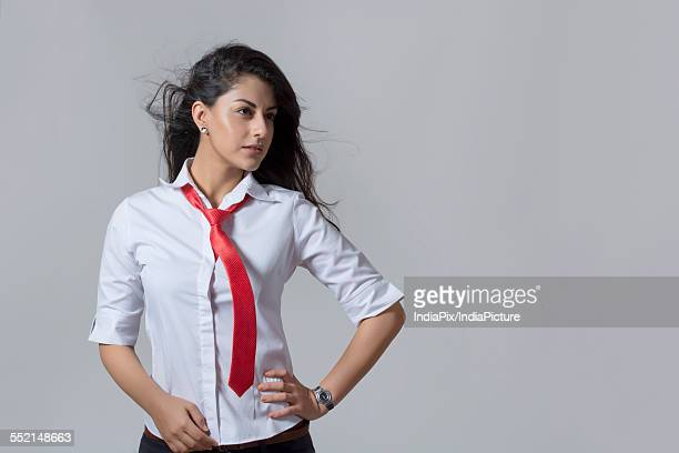 Confident Indian fashionable businesswoman with hand on hip standing against gray background