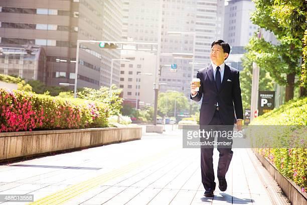 自信に満ちた日本の会社員もコーヒーを片手にお仕事