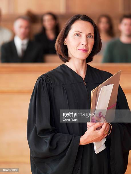Confident judge holding file in courtroom