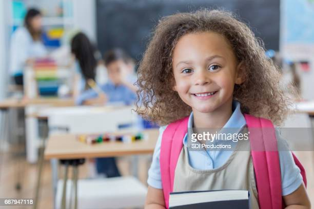 Confident kindergarten schoolgirl in her classroom