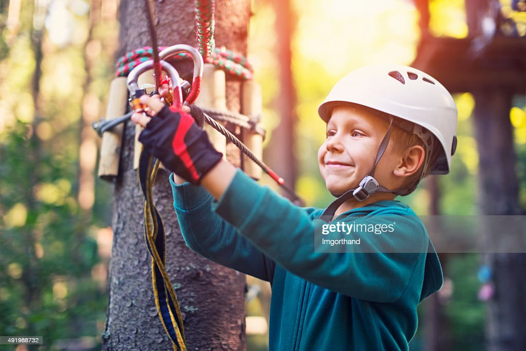 Confident little boy attaching a carabiner to zip line.