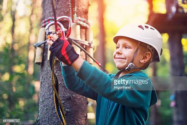 Confiant petit garçon attacher le mousqueton pour tyrolienne.