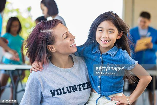 Confident little girl being held by woman wearing volunteer shirt