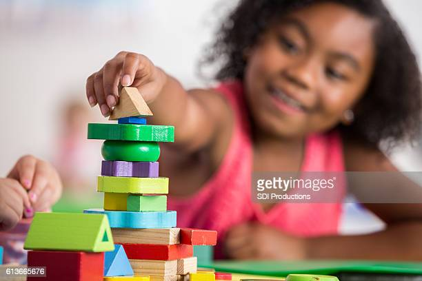 Confident little girl plays with blocks in preschool class