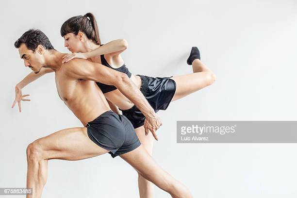 Confident male and female dancers against wall