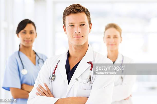 Confident Male Doctor With Colleagues In Hospital