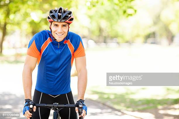 Confident Man In Sportswear Riding Bicycle At Park