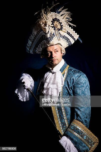 Confident Man In Venice Carnival Costume Against Black Background