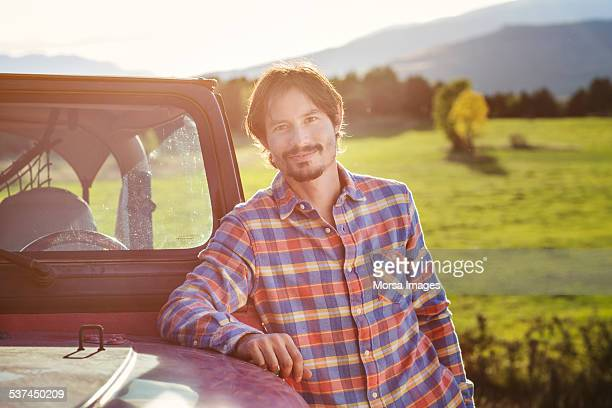 Confident man leaning on SUV