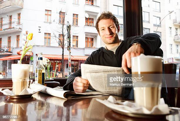 Confident man reading newspaper at cafe