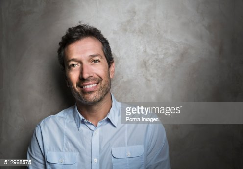 Confident man smiling against wall