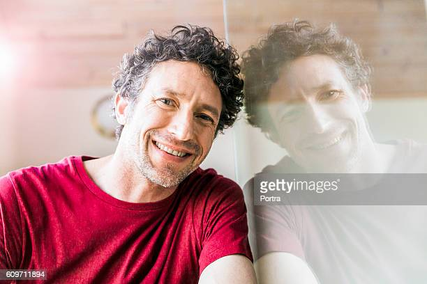 Confident man smiling while leaning on glass wall