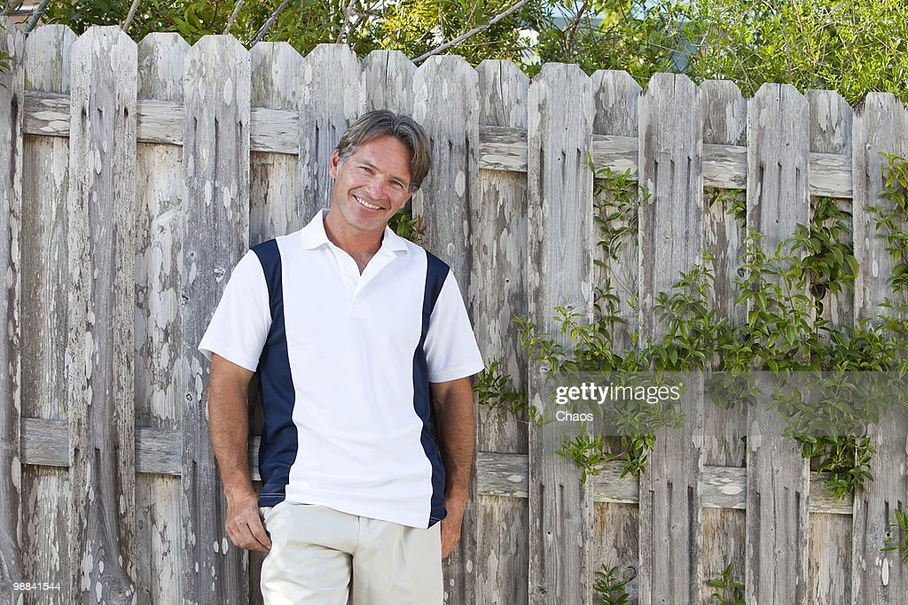 Confident man standing at a fence : Stock Photo