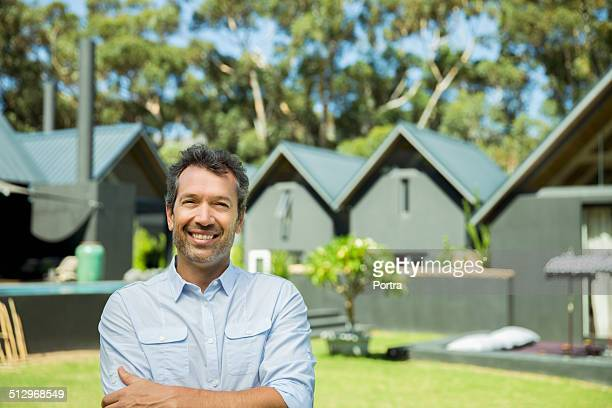 Confident man standing in lawn against resort