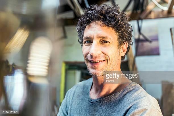 Confident manual worker smiling in workshop