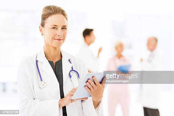 Confident Mature Female Doctor Using Digital Tablet In Hospital