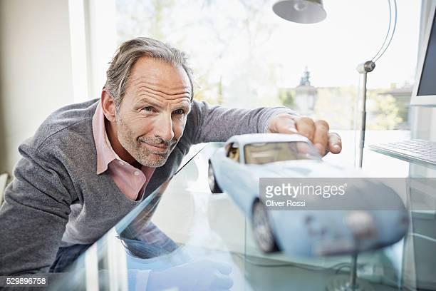 Confident mature man looking at model car