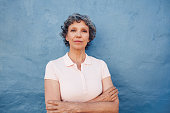 Portrait of confident mature woman standing with her arms crossed against blue background