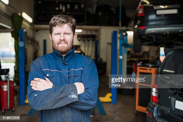 Confident mechanic with arms crossed in garage