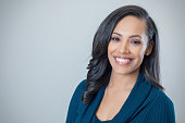Cheerful mixed race mid adult woman smiles confidently at the camera. Copy space available.