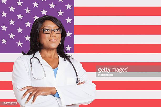 Confident mixed race female surgeon looking away over American flag