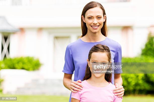 Confident Mother And Daughter In Front Garden