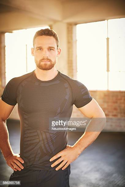 Confident muscular man standing with hands on waist in gym
