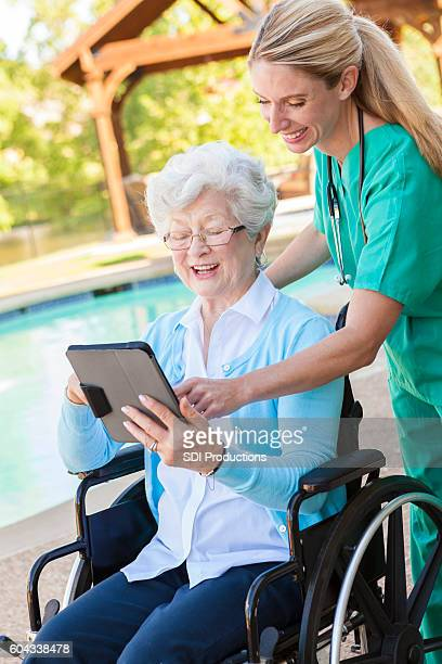 Confident nurse and her patient look at digital tablet