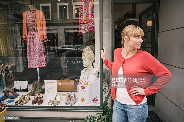Confident owner standing against store looking away with hand on hip