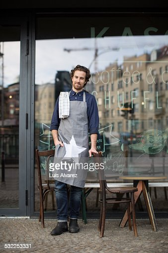 Confident owner standing outside coffee shop