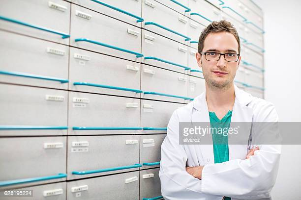 Confident pharmacist standing by a medicine shelf