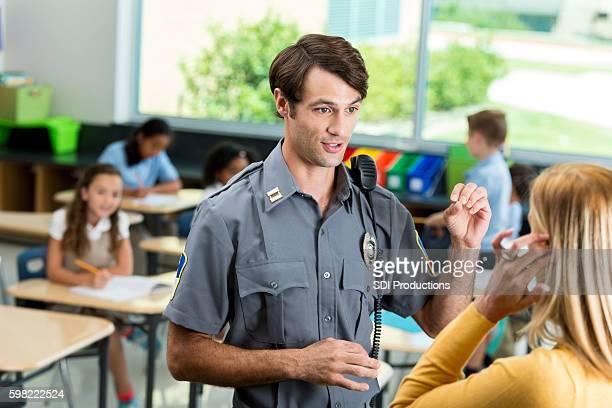 Confident police officer talks with school teacher