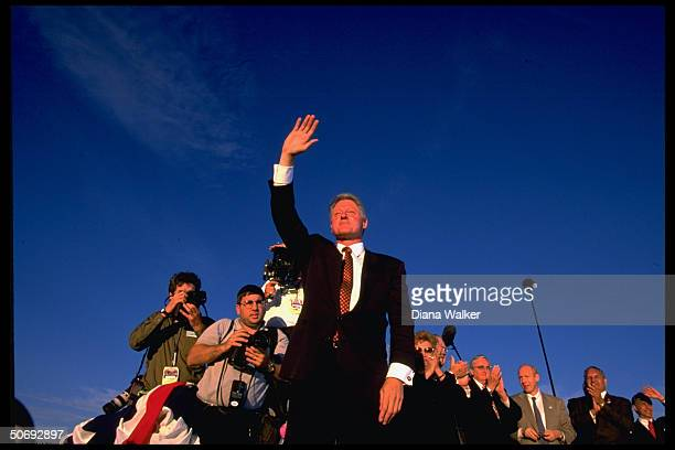 Confident Pres Bill Clinton waving to supporters during campaign rally few days before election press corps intow