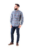 Confident relaxed bearded handsome fashion model in plaid shirt with thumbs in pockets looking away. Full body isolated on white background.